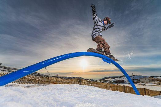 Snowboarder sliding on a rail