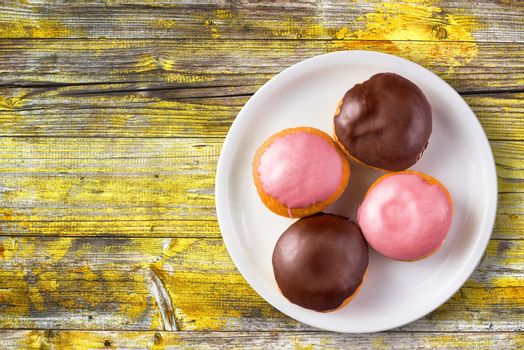 Doughnuts with sweet topping on a plate, top view