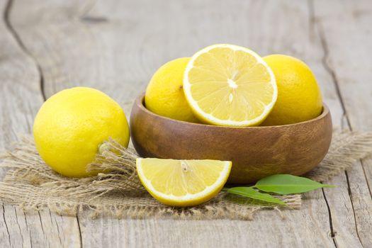 fresh lemons in a bowl on wooden background