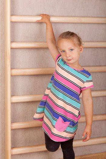 Cute girl hanging on wooden wall bar. Healthy lifestyle.