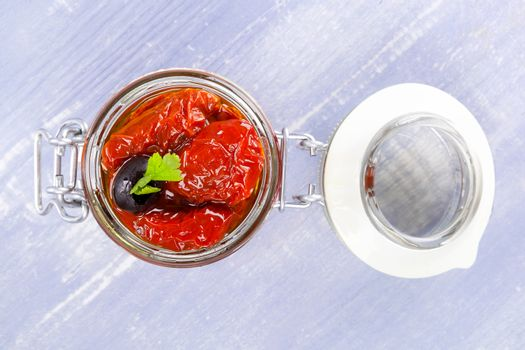 Dry tomatoes in oil in jar on blue wooden background. Culinary eating.