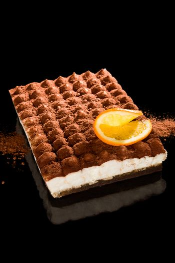 Delicious tiramisu dessert isolated on black background. Traditional sweet dessert.