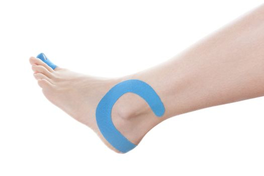 Therapeutic tape on female ankle isolated on white background. Chronic pain, alternative medicine. Rehabilitation and physiotherapy.