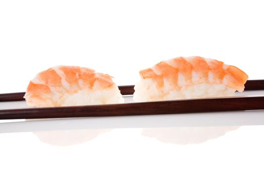 Delicious luxurious nigiri sushi with shrimp and chopsticks isolated on white background. Minimal contemporary asian style.
