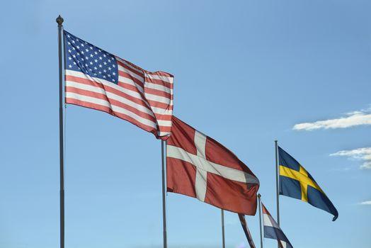 Flags, backlit on a clear sky.