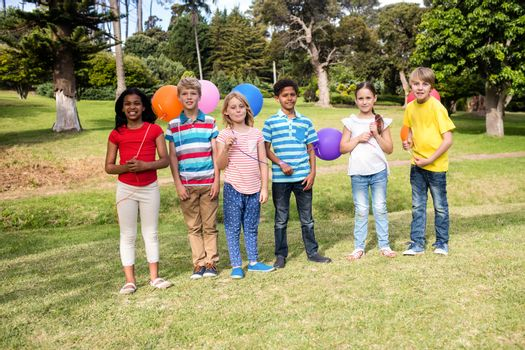 Children standing with balloons in the park