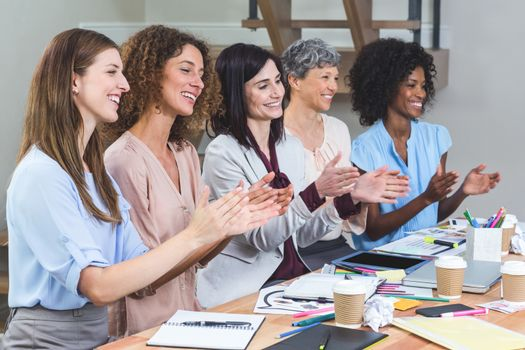 Group of interior designers applauding in office