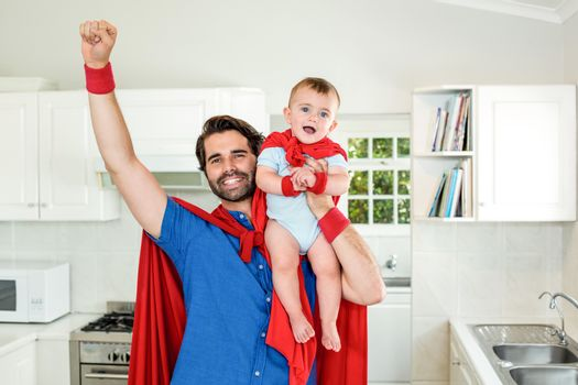 Father in superhero costume lifting son in kitchen