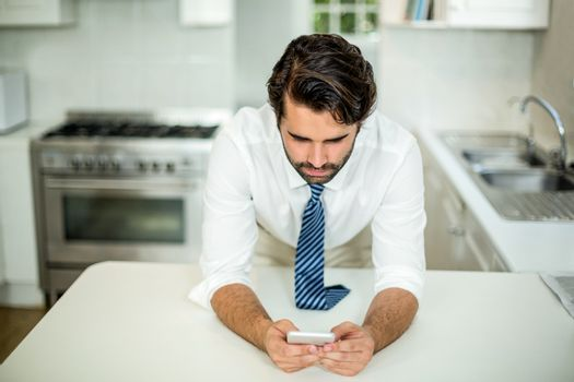 Businessman using cellphone at table in kitchen