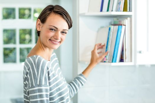 Beautiful woman picking book from cabinet at home