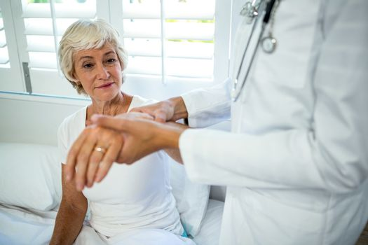 Midsection of doctor assisting senior woman