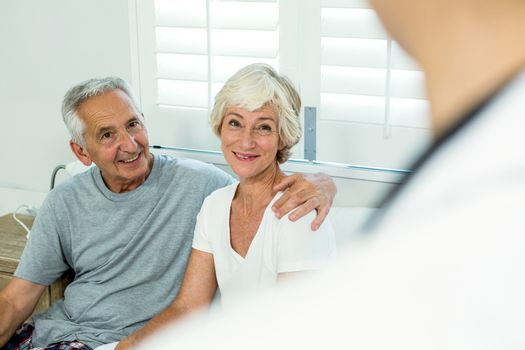 Smiling senior couple with doctor at home