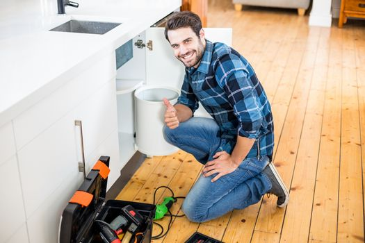 Man fixing kitchen sink giving thumbs up