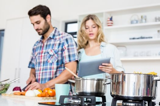 Young couple chopping vegetable and using digital tablet