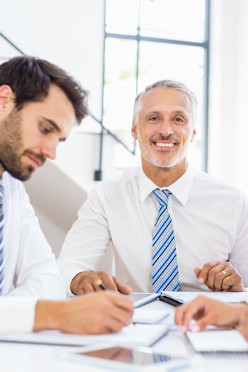 A businessman is smiling and posing and another worker is looking at his notes