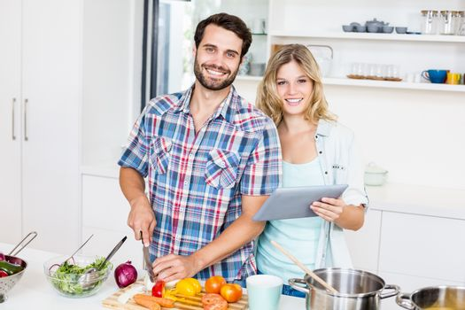 Young couple chopping vegetable and holding digital tablet