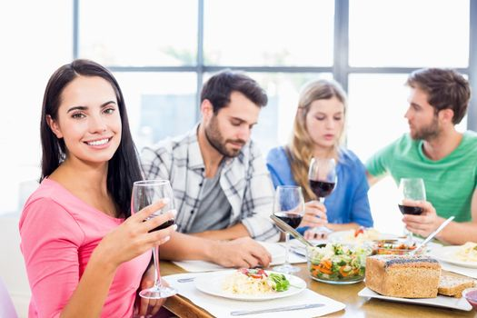 Portrait of woman holding wine glass having meal with friends