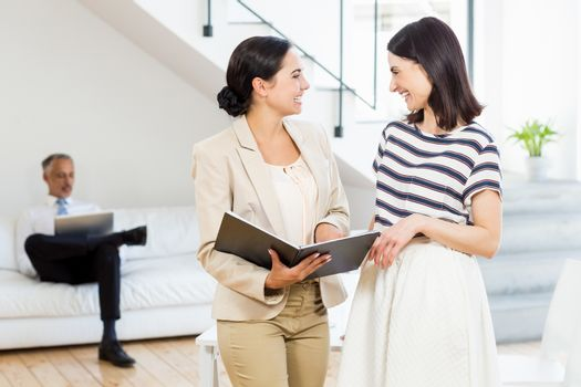 Businesswoman and a colleague interacting and holding diary