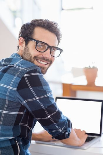 Happy young man using laptop at home