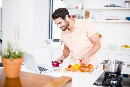 Man looking recipe on laptop