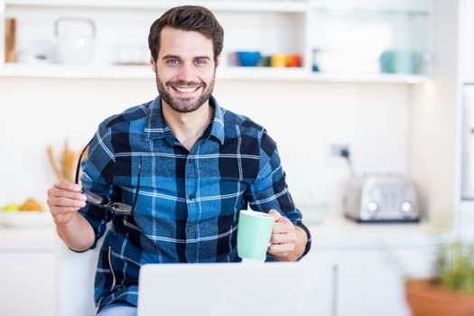 A man is holding his glasses and a mug