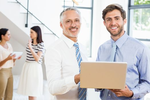 Two businessmen are smiling, posing and holding a laptop