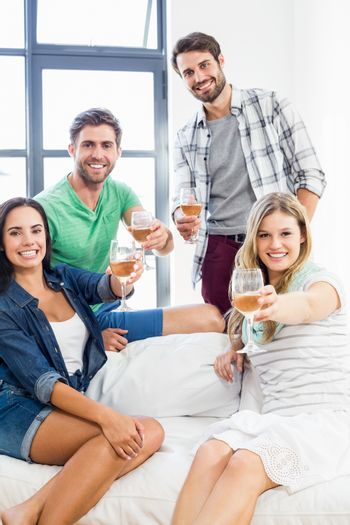 Smiling friends sitting on sofa drinking alcohol