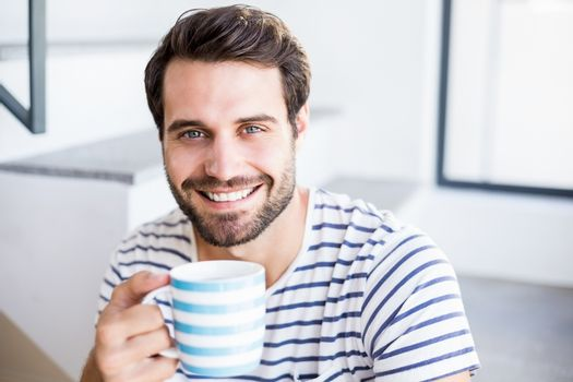 Portrait of happy man having cup of coffee