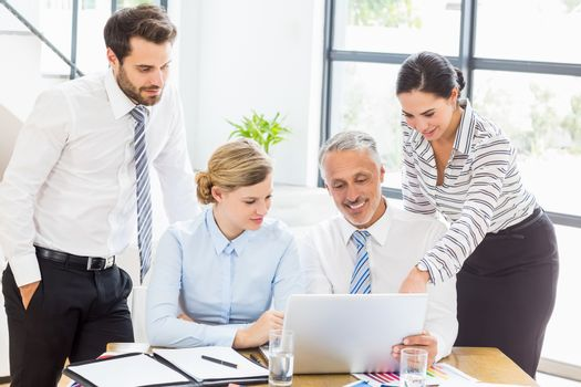 Business colleagues discussing office work on laptop