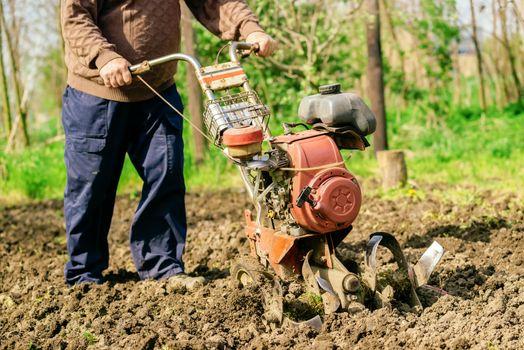 Man preparing garden soil with cultivator tiller