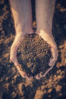 Farmer holding pile of arable soil