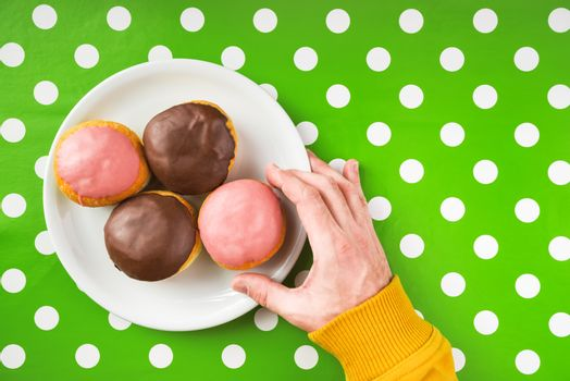 Hand picking donut with sweet strawberry topping from a plate