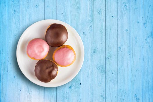 Top view of doughnuts with sweet topping on a plate