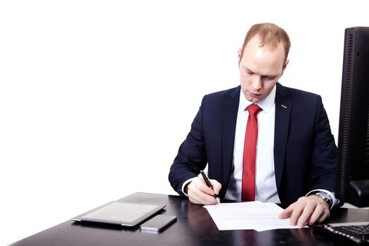 Businessman signs a contract in the workplace. On the table, computer, phone, tablet, mouse, keyboard. Isolated on white background