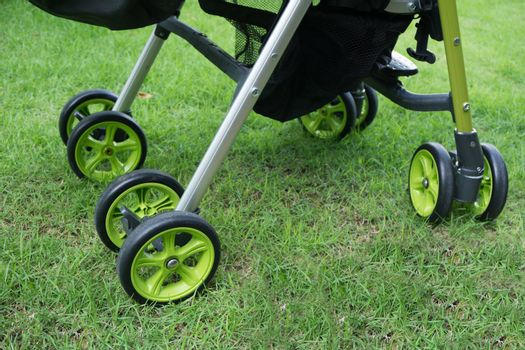 Detail of stroller for child on green grass