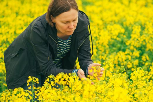 Female farmer in blooming rapeseed field