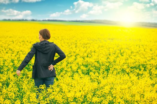Woman agronomist standing in field of blooming cultivated rapese