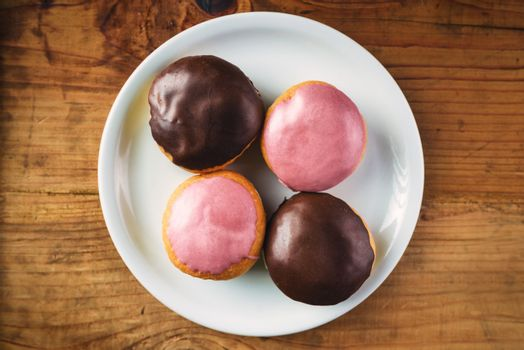 Donuts with sweet topping on a plate, top view