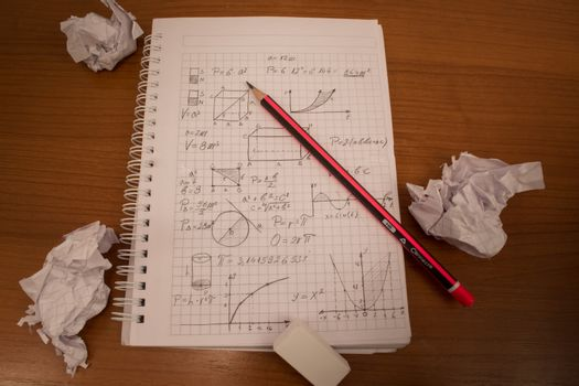 formulas on the notebook with crumpled paper all around