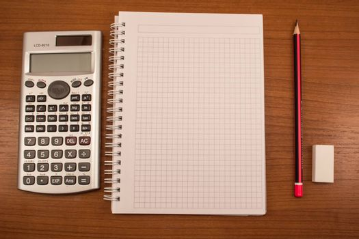 Calculator, pencil, eraser and notebook on the wooden table