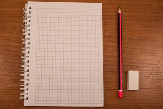 Pencil, eraser and notebook on the wooden table