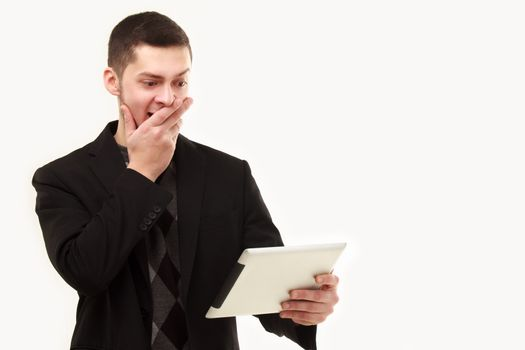Casual businessman surprisedly looking  at his tablet screen isolated on white