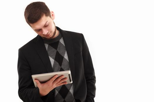 Casual businessman joyfully  looking  at his tablet screen  isolated on white