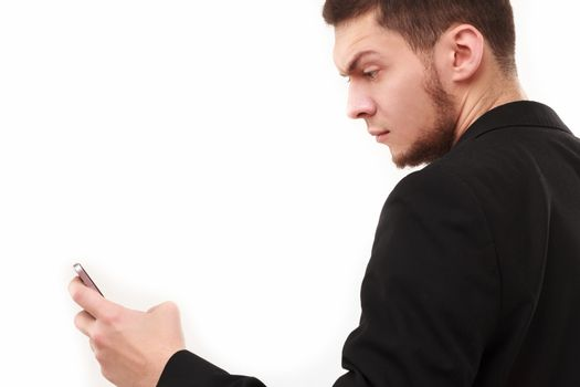 Businessman with a raised eyebrow using his phone isolated on white