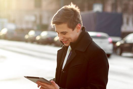 Young business man in black coat in street using tablet