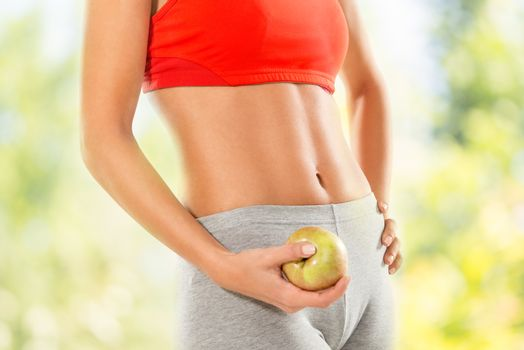 Close-up of a perfect woman body. Woman holding apple. Dieting concept.
