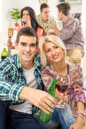 Young couple at home party with a smile on their faces, toasting with drinks that are in the foreground. In the background is they friends.