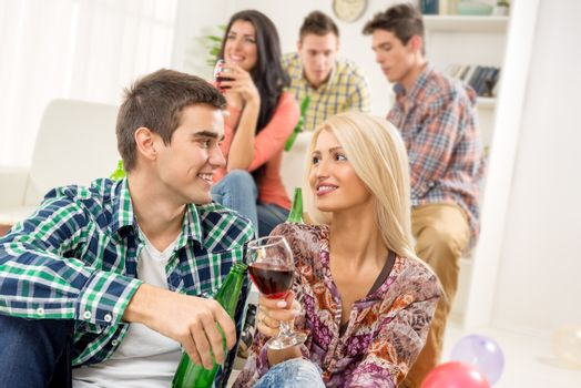 Young couple at a home party, sit on the floor, knocking the glasses toasting, in the background you can see friends.
