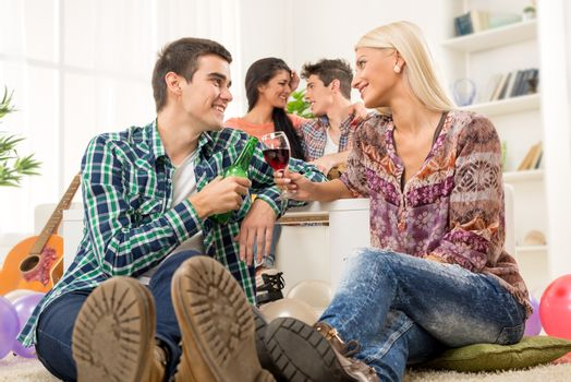 Young couple at a home party, sit on the floor, knocking the glasses toasting, in the background you can see another couple.