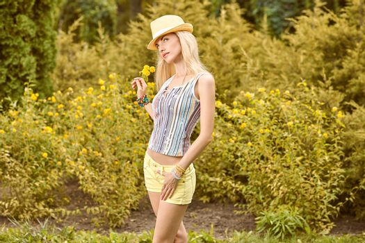 Beauty playful woman relax in summer garden dreaming, people, outdoors, bokeh. Attractive happy blonde girl in hat with flower enjoying nature, harmony on meadow, lifestyle.Sunny day, forest,copyspace